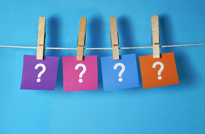 Hanging sticky notes with question marks on them, relating to the FAQ pages